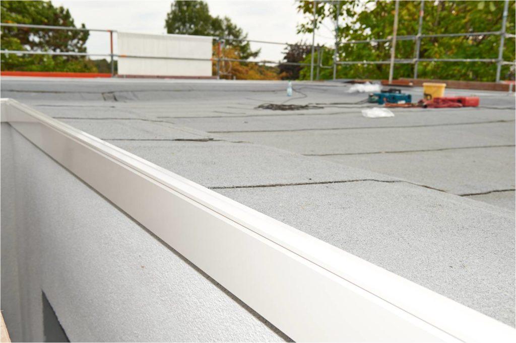 Mit einer Blecheindeckung der Attika wurde ein sauberer Übergang zwischen Flachdach und gedämmter Fassade geschaffen. Die Ausgestaltung des Flachdaches mit erkennbarem Gefälle zur Dachentwässerung hin soll verhindern, dass sich auf dem Dach stehendes Regenwasser sammelt. (Copyright: Deutsche Rockwool GmbH & Co. KG)