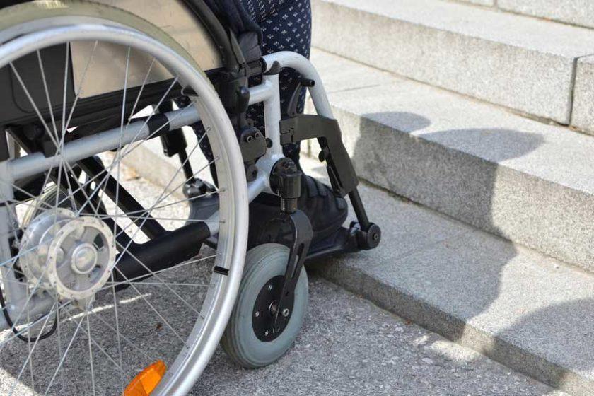 Gehbehinderte Frau im Rollstuhl von Stufen blockiert