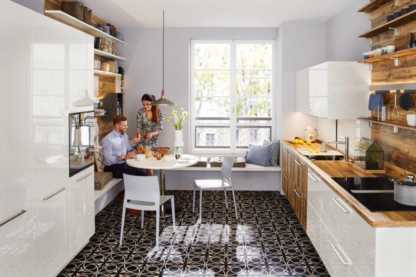 Das glänzend kühle Weiß zusammen mit dem warmen Holz geben dieser Küche das Wohlgefühl. (Foto: AMK)