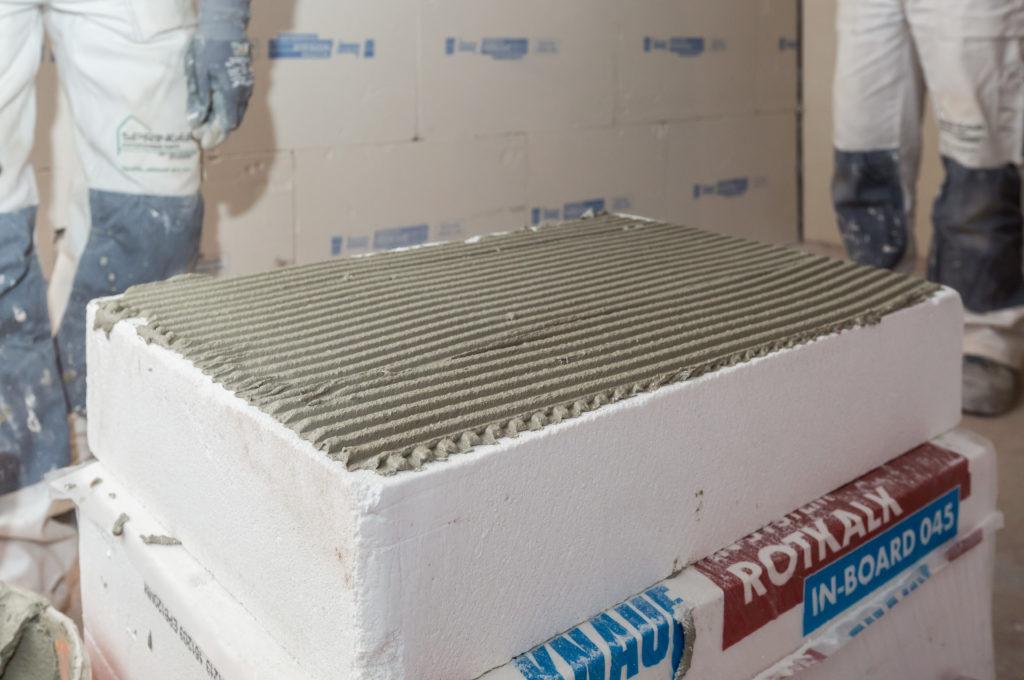 Vor der Wandmontage erhalten die Knauf Rotkalk in-Board Innendämmplatten ein ca. 5 mm dickflächiges Bett aus Knauf Rotkalk in-Klebemörtel, mit der Zahnspachtel aufgetragen. (Foto: Knauf/Stephan Klonk)