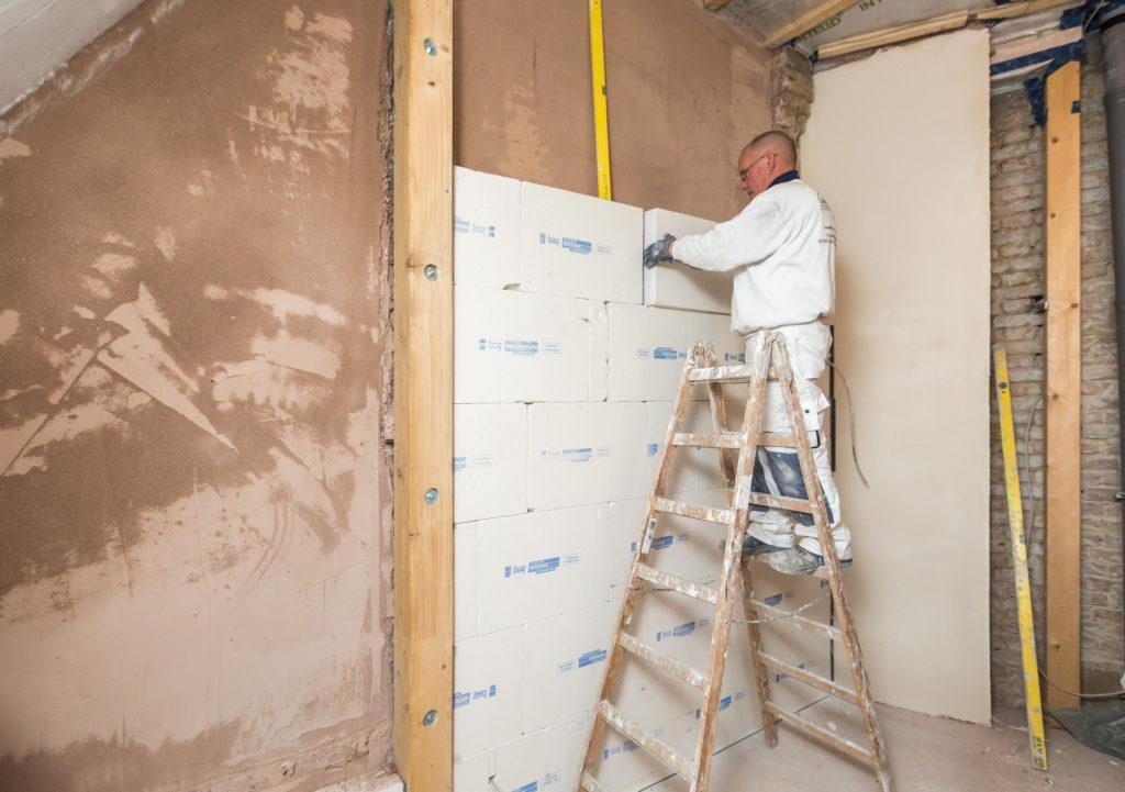 Auf die mit Rotkalk Grund egalisierte Wand wird das Innendämmsystem Knauf Rotkalk in-Board aus diffusionsoffenem Perlitgestein vollflächig verklebt. (Foto: Knauf/Stephan Klonk)