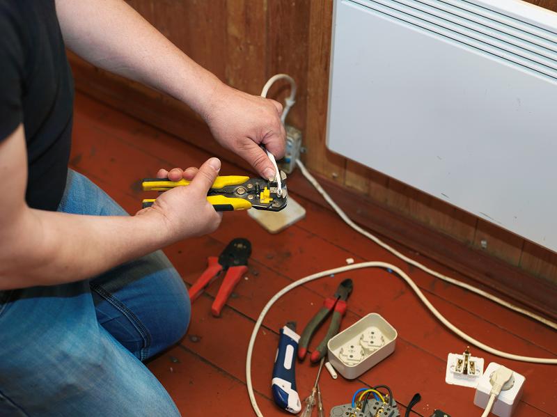 Handwerker mit Werkzeug und Ersatzteilen vor einer Elektroheizung