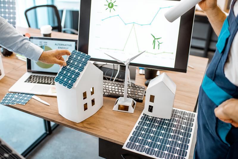 Mitarbeiter in einem Architekturbüro planen mit Computer und Modellen die optimale Dachausrichtung für Photovoltaik.