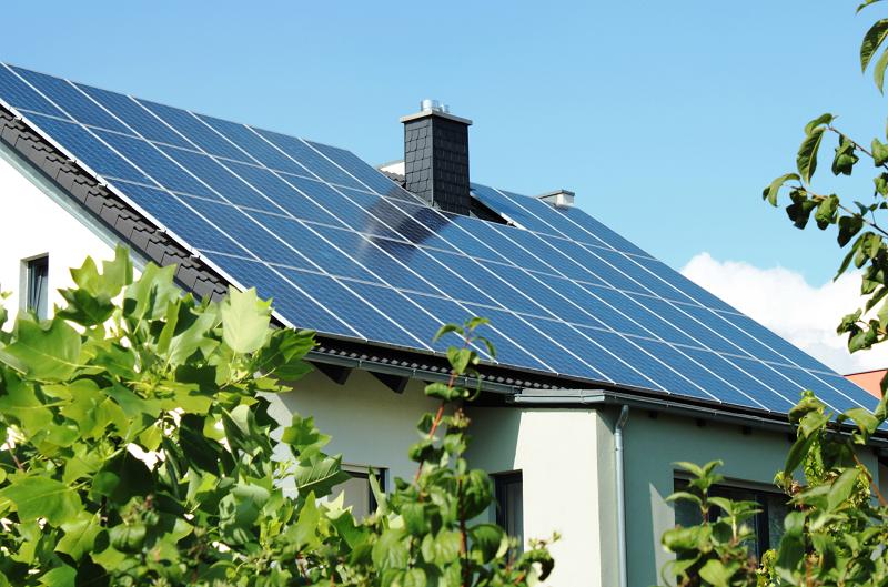 Einfamilienhaus mit einer komplett mit Photovoltaikmodulen eingedeckten Dachseite.