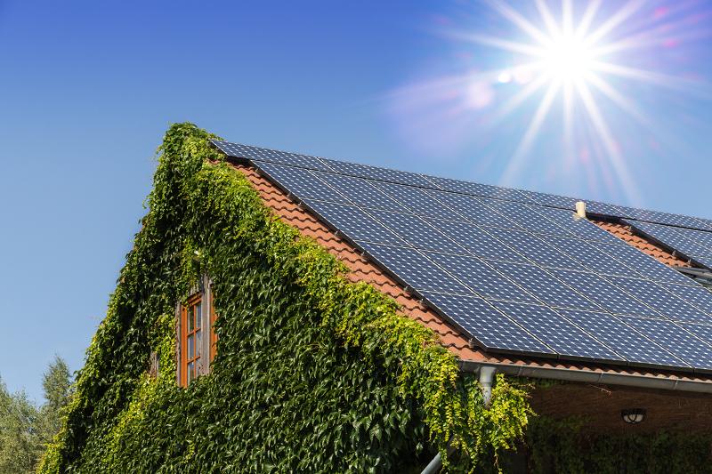 Photovoltaik-Anlage auf einem älteren Einfamilienhaus im Sonnenschein.