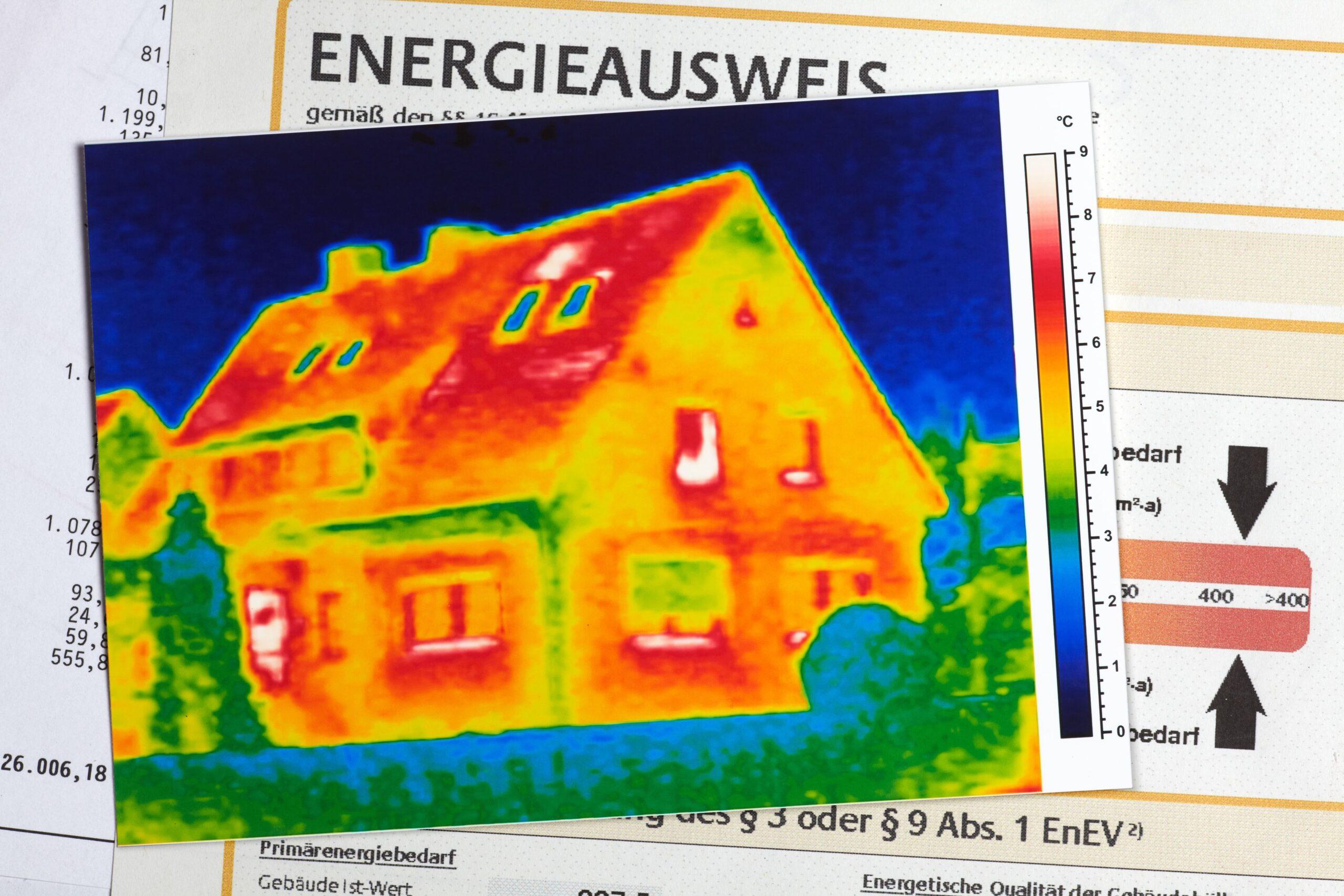 Thermografie einer ineffizienten Gebäudehülle auf einem Energieausweis liegend, der einen hohen Energiebedarf anzeigt